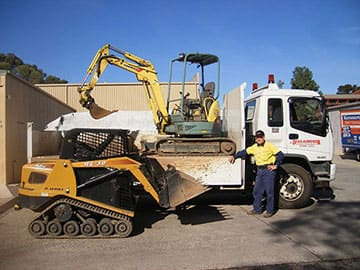 An Operator Stands Next To His Excavator, Digger And Tipper