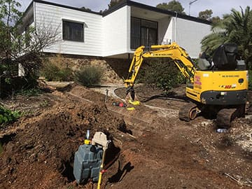 Contractor Digging Trench With A Mini Excavator