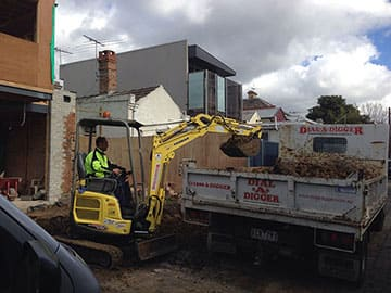 Mini Excavator digging up and removing concrete slabs and putting waste into a tipper truck