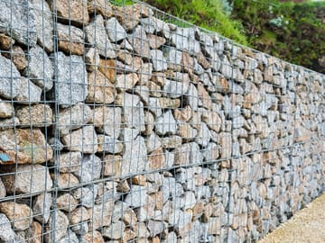 Excvator Clears Site For Retaining Wall Construction